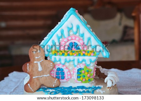 Gingerbread man at a gingerbread house  - stock photo