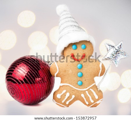 Gingerbread Man Christmas Cookie with Santa hat, magic stick and christmas red ball over defocused lights  background, closeup. - stock photo