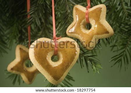 Gingerbread ornaments hanging on fir branch and isolated against green paper - stock photo