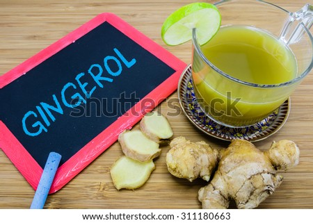 Gingerol, an active constituent of fresh ginger, written on chalkboard with ginger drink and fresh ginger root on wood background - stock photo