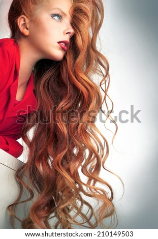 Girl advertises a beautiful curly red hair - stock photo