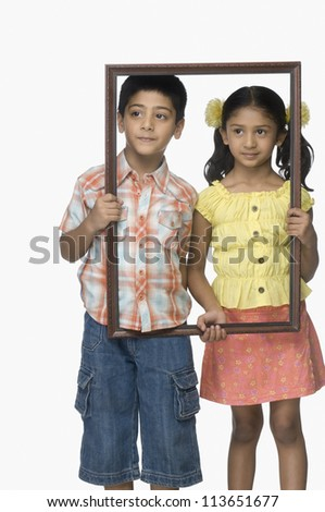 Girl and a boy holding an empty picture frame - stock photo