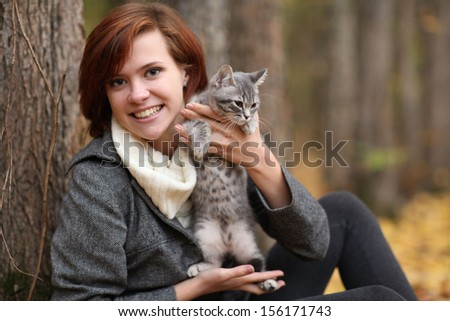 girl and a cat in the autumn park - stock photo
