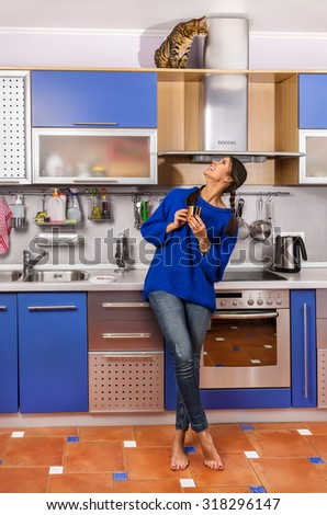 Girl and a cat in the kitchen. - stock photo