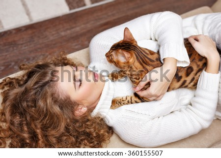 Girl and Bengal cat home. Home comfort. Girl and a cat lying on the couch. Girl hugging cat. - stock photo