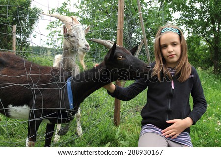 girl and black goat on the farm  - stock photo