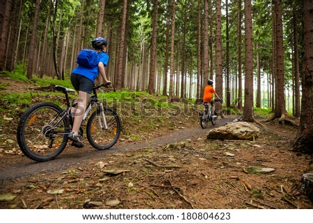 Girl and boy biking on forest trails  - stock photo