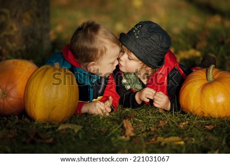 girl and boy kissing between the pumpkins - stock photo