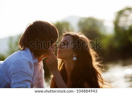 Girl and boy kissing on sunset - stock photo