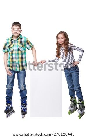 girl and boy on roller skates beside a white blank - stock photo