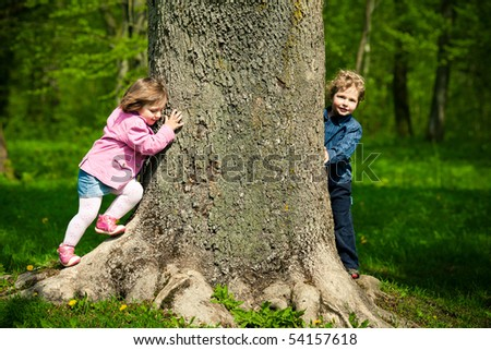 girl and boy playing hide and seek - stock photo