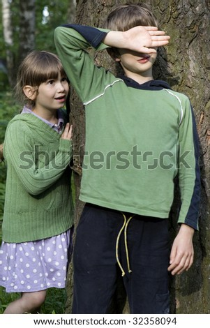 Girl and boy playing hide-and-seek. Boy close his eyes by hand - stock photo