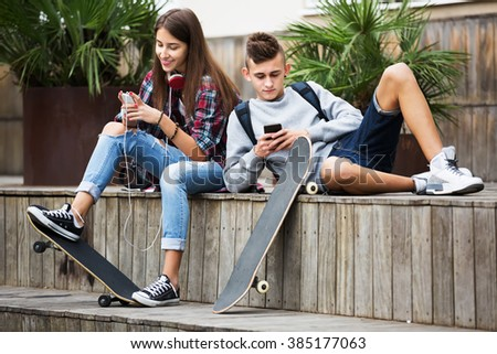 Girl and boy teens playing on mobile phones and listening to music outdoors - stock photo