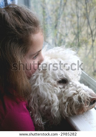 Girl and dog looking out of a window - stock photo