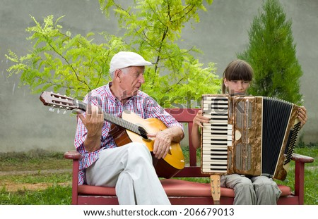 Girl and grandpa playing musical instruments in garden - stock photo