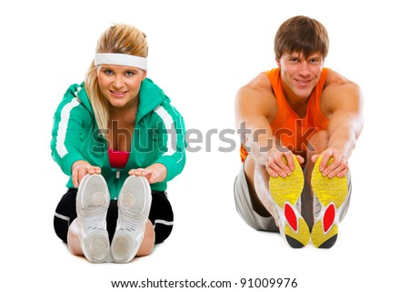 Girl and guy in sportswear sitting on floor and making stretching exercises isolated on white - stock photo