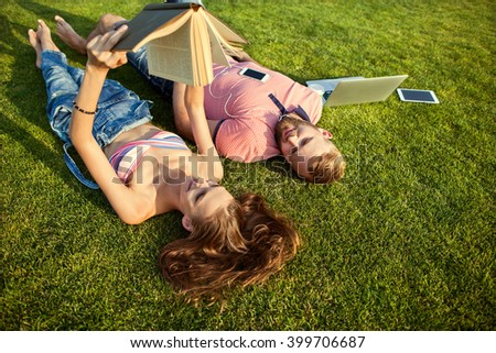 girl and guy lying on the grass reading a book relaxing in the park  - stock photo