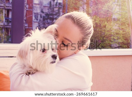 Girl and her dog in coffeehouse kissing and relaxing - stock photo
