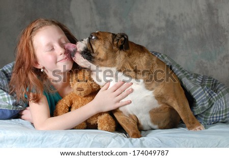 girl and her dog - pre teenage girl ready for cuddling with her dog - english bulldog - stock photo