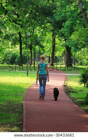 girl and her dog walking in the countryside - stock photo