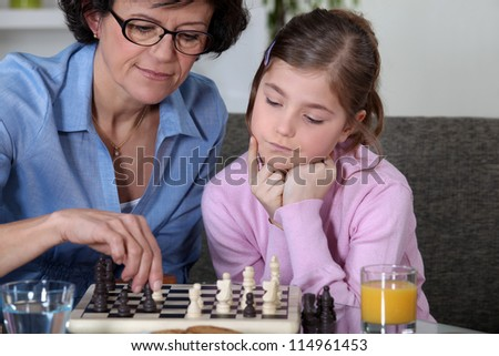 Girl and her grandmother playing chess - stock photo