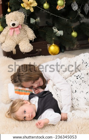 girl and her younger brother sleeping at christmas tree indoors - stock photo