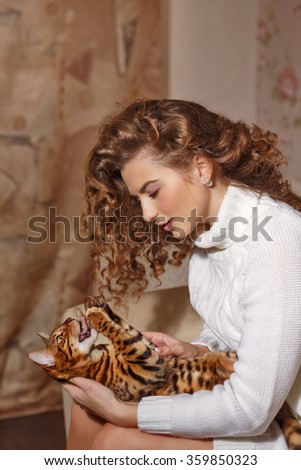 Girl and leopard cat home. Home comfort. Girl scratching cat. - stock photo
