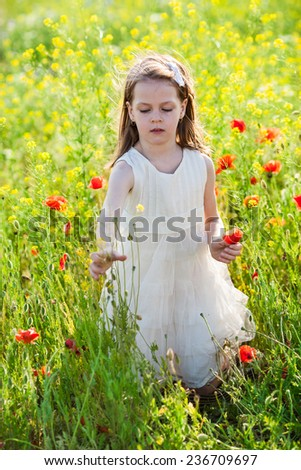 Girl and meadow flowers. Sweet little girl in a white dress in the poppy seed meadow with wild spring flowers - stock photo
