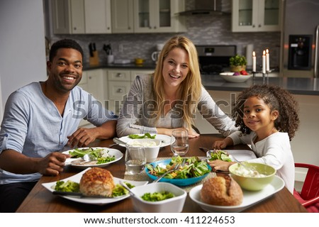 Girl and mixed race parents dine in their kitchen, to camera - stock photo