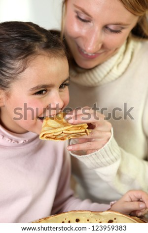 Girl and mom eating pancakes - stock photo