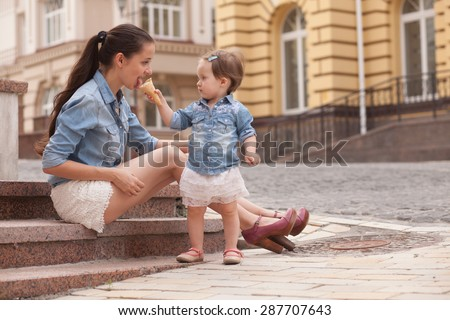 girl and mother have fun with ice cream on street - stock photo