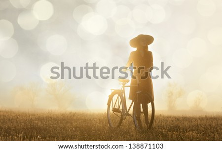 Girl and on a bike in the countryside in sunrise time - stock photo