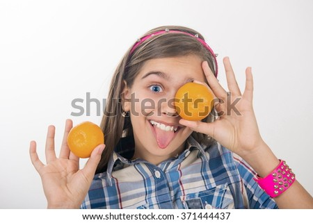 Girl and tangerines. cheerful teen girl holding oranges near the face. ?ealthy girl with vitamins in the form of citrus fruits - stock photo