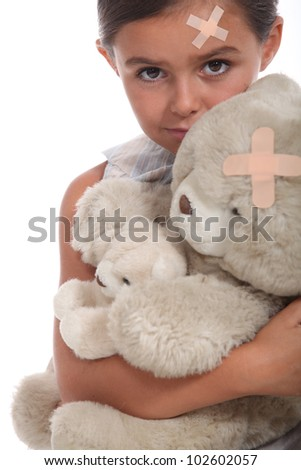Girl and teddy with a plaster on forehead - stock photo