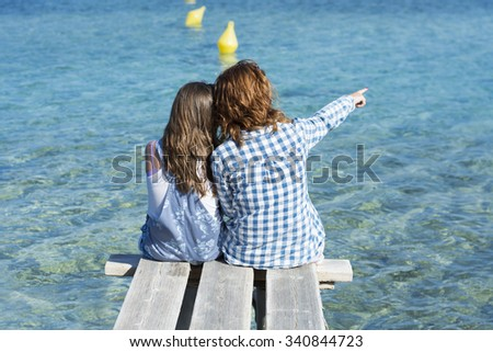 Girl and woman contemplating the sea - stock photo