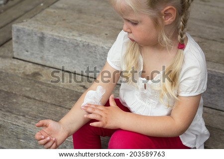 Girl applying dermatology cream on skin - stock photo