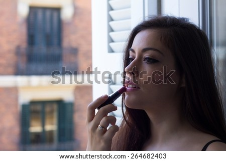 Girl applying lipstick in a balcony. - stock photo