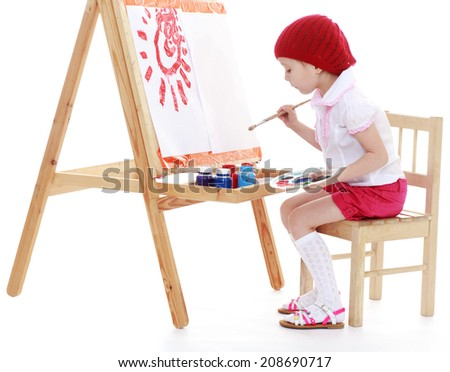 Girl artist sitting at his easel and paints the sun isolated on a white. Summer fun, the concept of happiness and family wellbeing. - stock photo