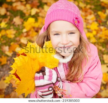 Girl at autumn. Little child outdoors - stock photo