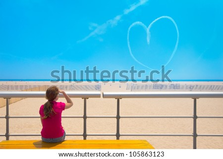 Girl at beach on bright sunny day viewing heart shaped skywriting - stock photo