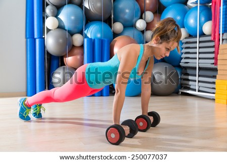 Girl at gym push-up strength pushup exercise with dumbbells workout - stock photo