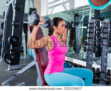 girl at gym seated dumbbell shoulder press workout exercise - stock photo