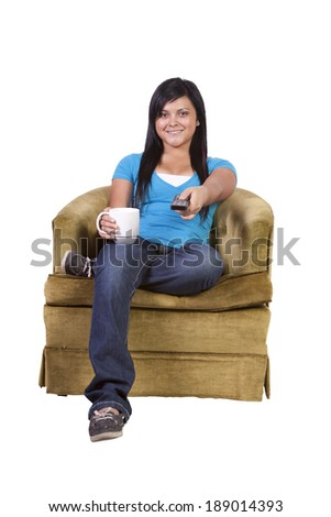 Girl at Home watching tv with a remote control  - stock photo