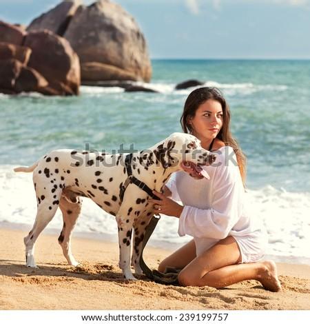 girl at sea with the dog Dalmatian - stock photo