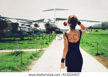 Girl at the airport looking on aircraft.Go to travel - stock photo