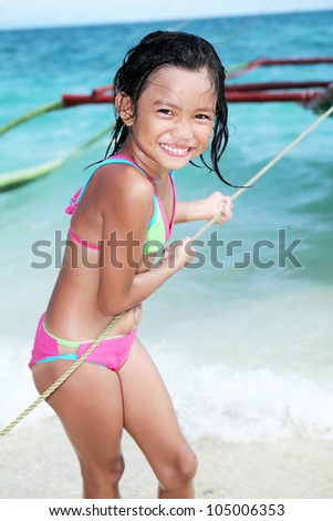 Girl at the beach pulling a rope from a wooden boat. - stock photo