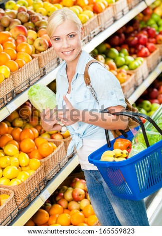 Girl at the market choosing fruits and vegetables hands cabbage and full of purchases hand cart and thumbs up - stock photo
