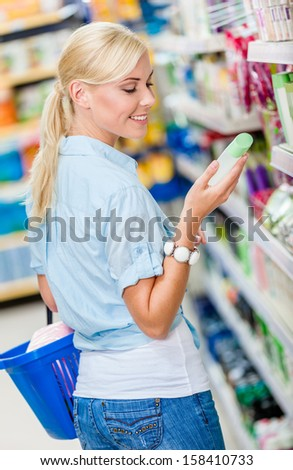 Girl at the store choosing cosmetics among the great variety of products. Concept of consumerism, retail and purchase - stock photo