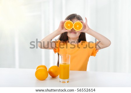 girl at the table with oranges and juice. - stock photo