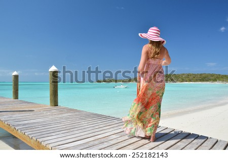 Girl at the wooden jetty looking to the ocean. Exuma, Bahamas - stock photo